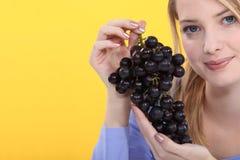 Manojo de la explotación agrícola de la mujer de uvas Imagenes de archivo