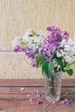 Manojo de la lila en un florero en el fondo de madera Diseño vida Pascua todavía de la flor violeta y blanca o de la frontera her Fotos de archivo libres de regalías