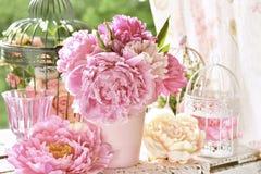 Manojo de la peonía en florero en la tabla en el jardín con efecto del color imagenes de archivo