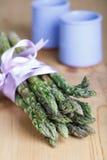Manojo de lanzas verdes frescas del espárrago atadas con la cinta de la lila Imagen de archivo libre de regalías
