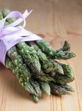 Manojo de lanzas verdes frescas del espárrago atadas con la cinta de la lila Foto de archivo