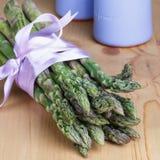 Manojo de lanzas verdes frescas del espárrago atadas con la cinta de la lila Imágenes de archivo libres de regalías