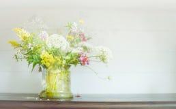 Manojo de las flores salvajes en el pote de cristal en estante de madera en el fondo ligero Decoración casera floral foto de archivo