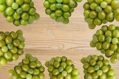 Manojo de las uvas verdes en la cesta, frutas del otoño, un símbolo de la abundancia en fondo de madera rústico con el espacio de imagenes de archivo