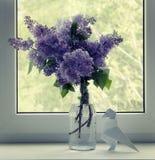 Manojo de lilas en un travesaño de la ventana y figura de la papiroflexia de un cuervo Imagenes de archivo