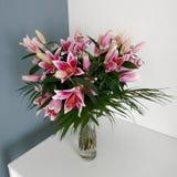 Manojo de lirios rosados en un florero cristalino imagen de archivo libre de regalías