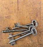 Manojo de llaves antiguas grandes en la tabla de madera Imagen de archivo