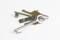 Manojo de llaves del metal de diversa forma en el fondo blanco Fotografía de archivo