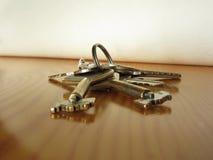 Manojo de llaves gastadas de la casa en la tabla de madera Imagenes de archivo