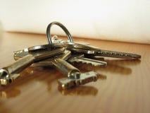Manojo de llaves gastadas de la casa en la tabla de madera Imagen de archivo