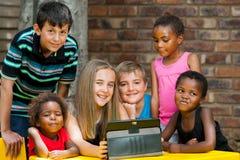 Manojo de niños que juegan en la tableta. Foto de archivo
