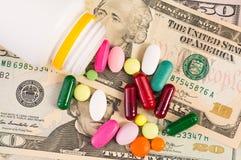Manojo de píldoras en billetes de dólar imagenes de archivo