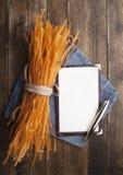 Manojo de pastas crudas de los tallarines con el papel del cuaderno Imágenes de archivo libres de regalías