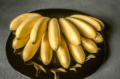 Manojo de pequeños plátanos maduros sin pelar en plato negro Imágenes de archivo libres de regalías