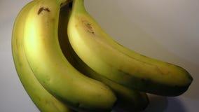 Manojo de plátanos que giran en la base blanca almacen de metraje de vídeo