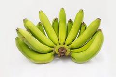 Manojo de plátanos verdes aislados en el fondo blanco Imagen de archivo