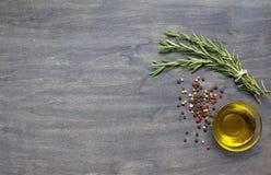 Manojo de romero, de condimento y de aceite de oliva en el backgro de madera Fotografía de archivo