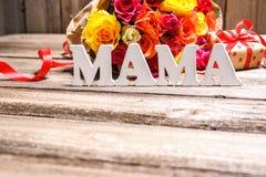 Manojo de rosas con una caja de regalo y una mamá de la palabra imagenes de archivo