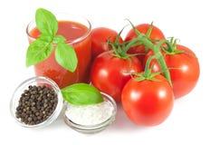 Manojo de tomates frescos con las hojas de la albahaca, el vidrio de jugo de tomate y los cuencos con pimienta negra y sal del ma Imagenes de archivo