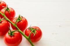 Manojo de tomates orgánicos frescos en el fondo blanco Foto de archivo