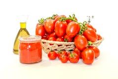 Manojo de tomates rojos en una cesta con aceite de oliva y jugo de tomate Imagenes de archivo