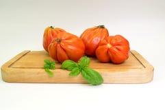 Manojo de tomates rojos en una cesta con aceite de oliva y jugo de tomate Imágenes de archivo libres de regalías