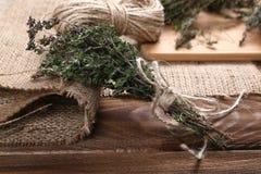 Manojo de tomillo orgánico en la tabla de madera Foto de archivo