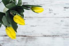 Manojo de tulipanes amarillos en la tabla de madera Foto de archivo