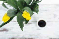 Manojo de tulipanes amarillos en la tabla de madera con la taza de té blanco Imagen de archivo