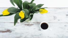 Manojo de tulipanes amarillos en la tabla de madera con la taza de té blanco Foto de archivo