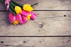 Manojo de tulipanes amarillos y rosados frescos de la primavera en el vintage de madera Fotos de archivo libres de regalías