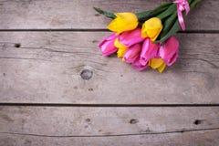 Manojo de tulipanes amarillos y rosados frescos de la primavera en el vintage de madera Fotos de archivo
