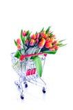 Manojo de tulipanes naranja-amarillos en un carro de la compra Fotos de archivo libres de regalías