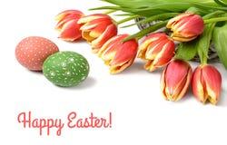 Manojo de tulipanes rayados y de dos huevos de Pascua en el fondo blanco Imágenes de archivo libres de regalías