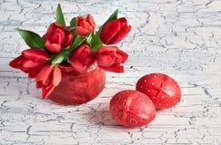 Manojo de tulipanes rojos y de dos huevos de Pascua rojos en la parte posterior rústica blanca Fotografía de archivo libre de regalías