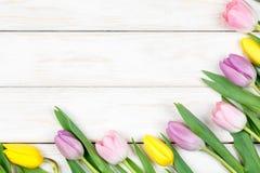 Manojo de tulipanes rosados y amarillos que mienten en un backgrou de madera blanco Fotografía de archivo libre de regalías