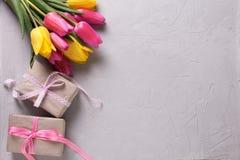 Manojo de tulipanes y de cajas con los presentes en backgr gris texturizado Foto de archivo libre de regalías