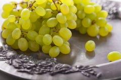 Manojo de uvas blancas en una bandeja Fotos de archivo