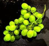 Manojo de uvas en una piedra negra de la pizarra Imagenes de archivo