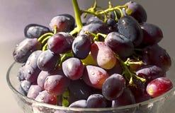 Manojo de uvas maduro en un primer transparente del cuenco Imagenes de archivo