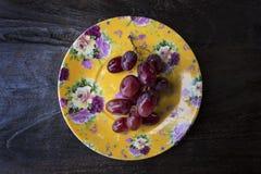 Manojo de uvas rojas maduras y jugosas lavadas en la vid aislada en una placa amarilla adornada colocada contra una tabla de made imágenes de archivo libres de regalías
