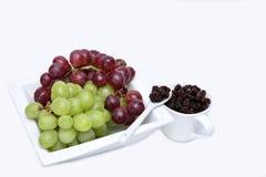 Manojo de uvas rojas y verdes y de pasas negras Foto de archivo libre de regalías