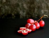 Manojo de uvas rosadas en un fondo negro fotos de archivo libres de regalías