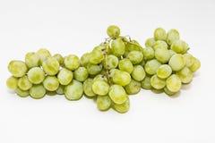 Manojo de uvas sin semillas verdes en un fondo blanco Fotos de archivo libres de regalías