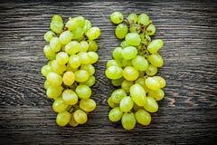 Manojo de uvas verdes en concepto de la comida del tablero de madera Fotos de archivo