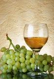 Manojo de uvas y de vino blanco Fotografía de archivo
