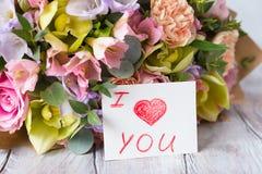 Manojo en colores pastel de las flores en un fondo ligero de madera con la etiqueta Lo i Imagen de archivo