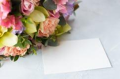 Manojo en colores pastel de las flores en un fondo de madera con Empty tag copia Imagen de archivo