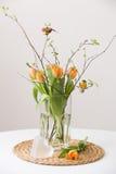 Manojo fresco de la primavera de tulipanes y hojas anaranjadas del verde y dos pequeños pájaros en un florero de cristal cristal  Imágenes de archivo libres de regalías