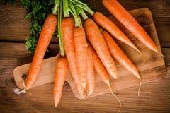 Manojo fresco de las zanahorias en tabla de cortar imagenes de archivo